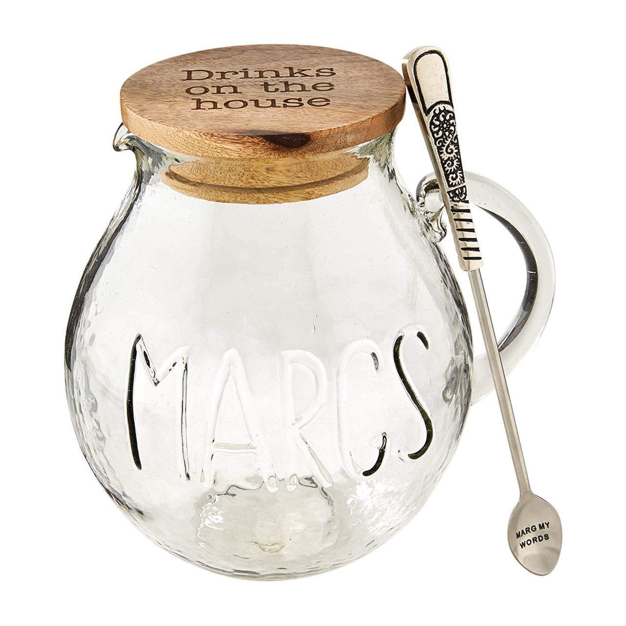 """Marg my words - you'll love our glass margarita pitcher set. The two piece set comes with a """"MARGS"""" embossed glass pitcher that has an etched mango wood lid that reads """"Drinks on the house"""". The set also arrives with a silver-plated spoon for mixing that reads """"MARG MY WORDS""""."""