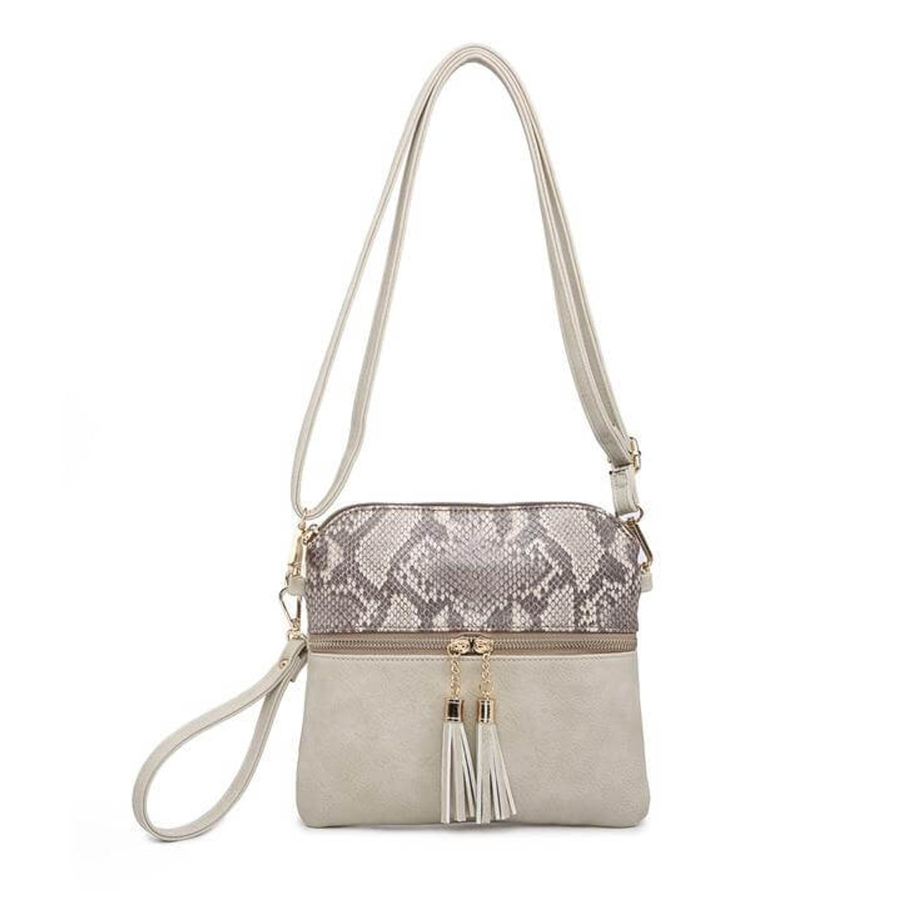 This zippered, tassel bag has a removable/adjustable shoulder strap, gold tone hardware, and a zipper top closure. It also zipper pockets on front and back; inside has a zipper pocket and a slip pocket.