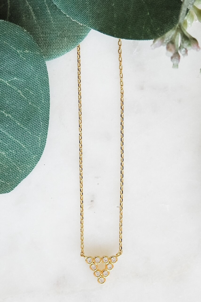 """Gold dipped dainty necklace attached to down-pointing triangle charm made up of 10 tiny gems in round mountings. Adjustable from 16"""" - 18"""" with lobsterclaw clasp. Heart charm at clasp. Nickel and lead free."""