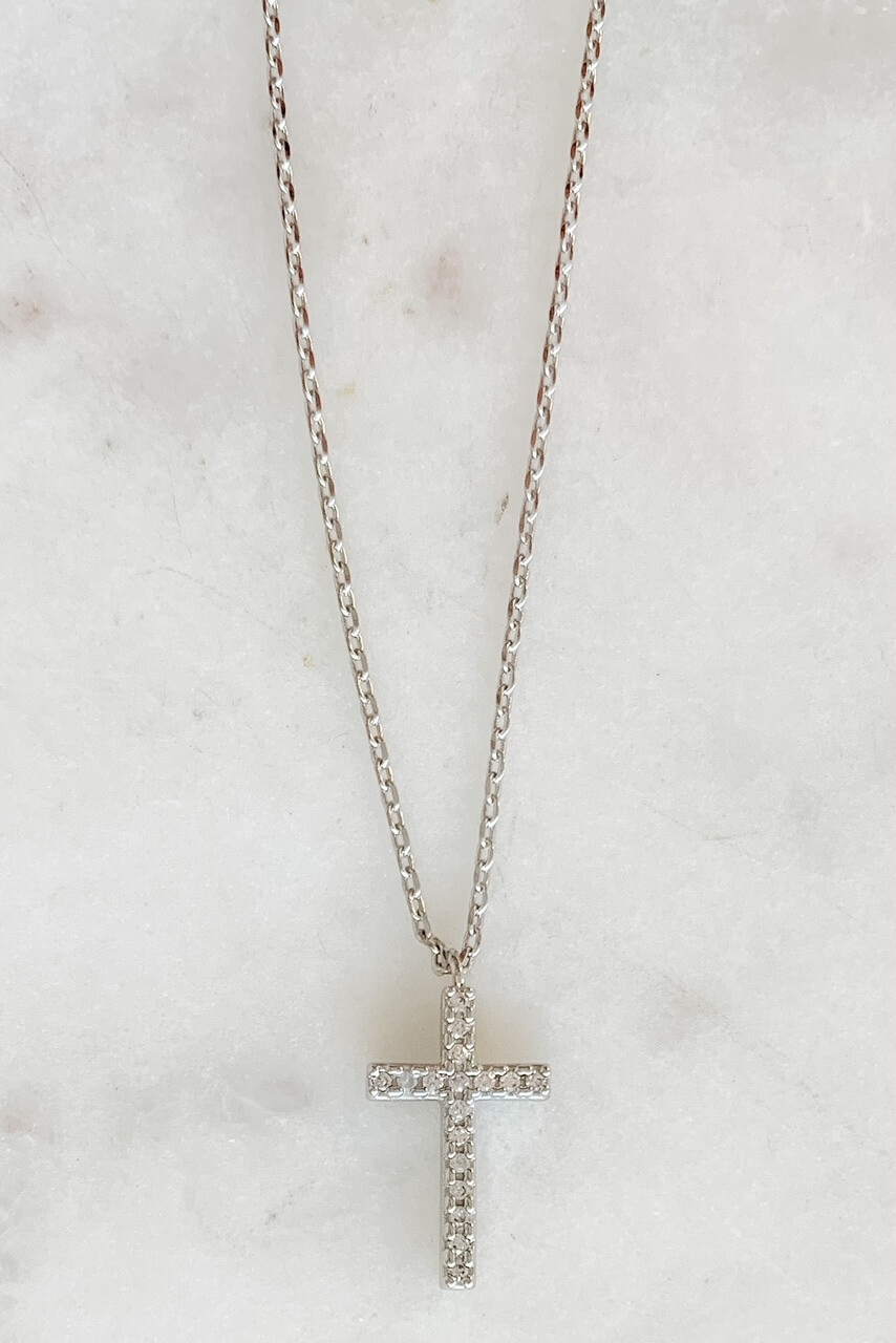 """White gold dipped dainty necklace attached to 5/8"""" sparkly cross charm. Adjustable from 15"""" - 17"""" with lobsterclaw clasp. Nickel and lead free."""