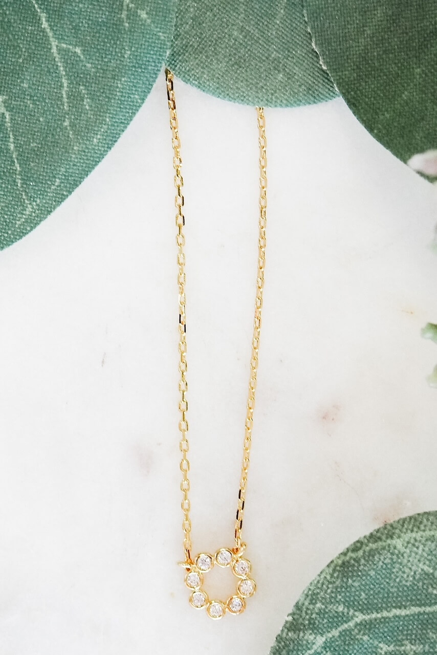 """Gold dipped dainty necklace attached a 3/8"""" circle charm made up of 8 tiny gems in round mountings. Adjustable from 15 1/2"""" - 17 3/4"""" with lobsterclaw clasp. Heart charm at clasp. Nickel and lead free."""