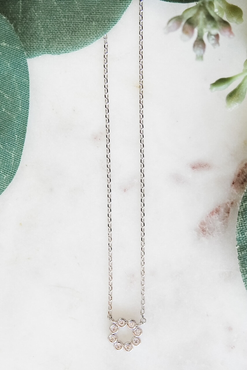 """White gold dipped dainty necklace attached to a 3/8"""" circle charm made up of 8 tiny gems in round mountings. Adjustable from 15 1/2"""" - 17 3/4"""" with lobsterclaw clasp. Heart charm at clasp. Nickel and lead free."""