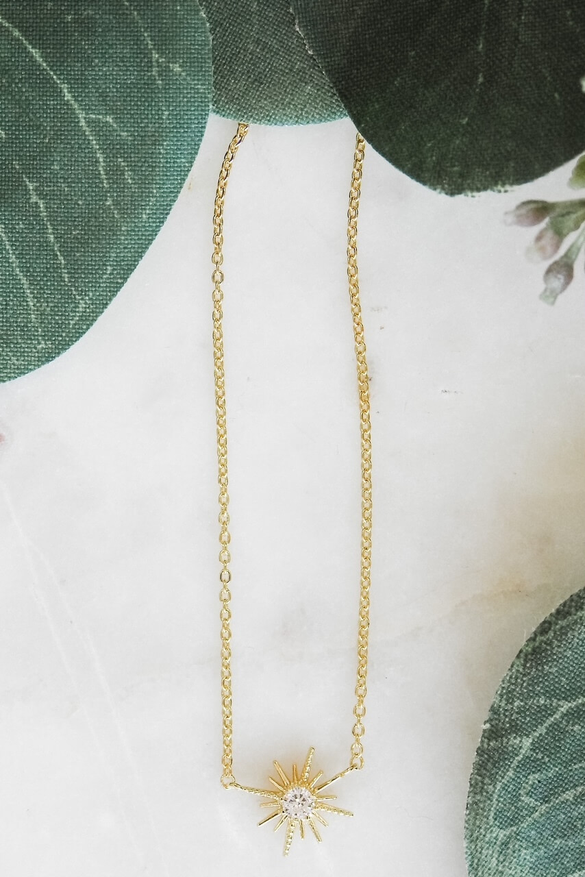 """Gold dipped dainty necklace attached to a 1/2"""" starburst charm with a tiny gem in the center. Adjustable from 15 1/2"""" - 17 1/4"""" with lobsterclaw clasp. Heart charm at clasp. Nickel and lead free."""