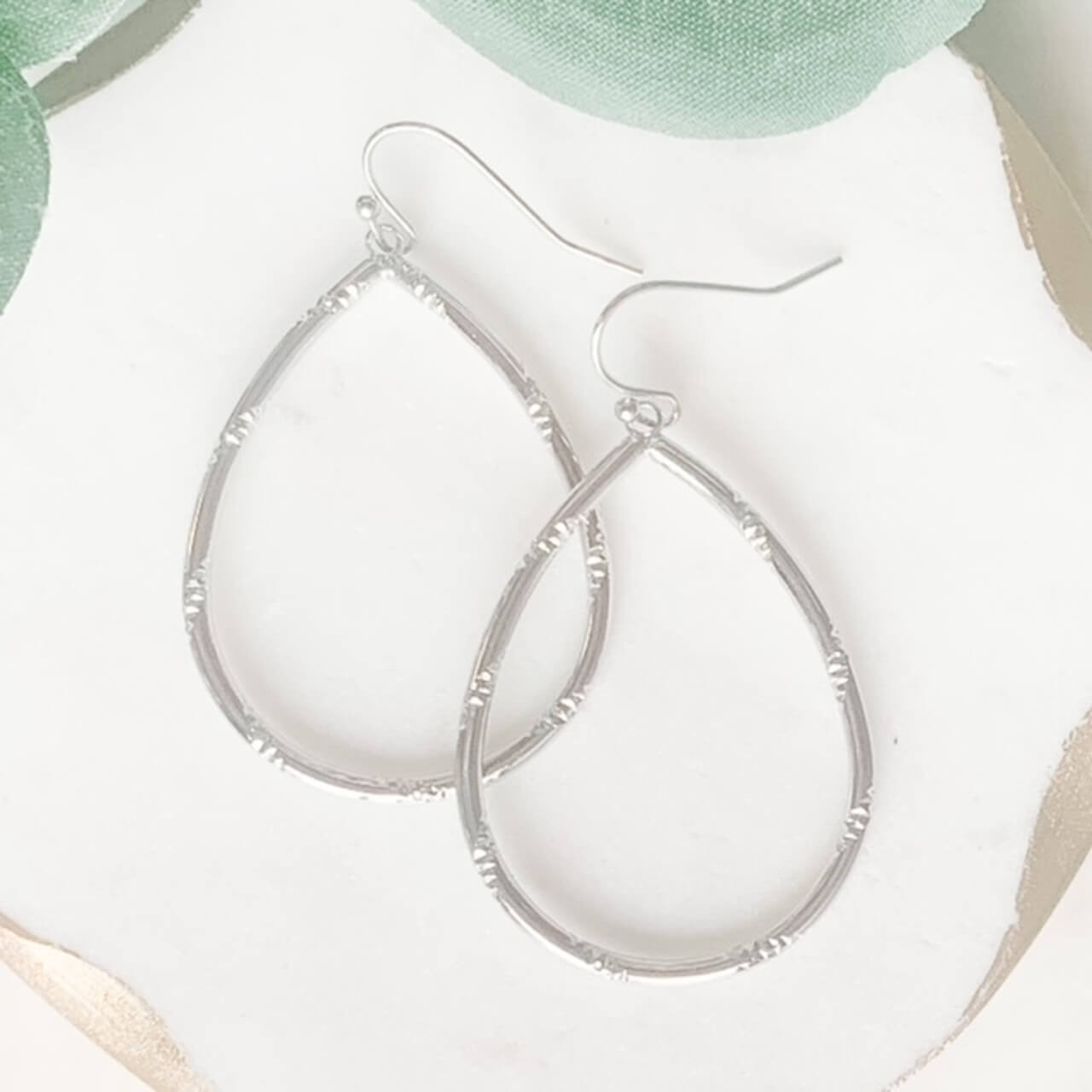 """Shiny silver teardrop shaped earrings with diamond-cut texture wrapping diagonally around the hoop. 2""""; hook back; nickel and lead free."""