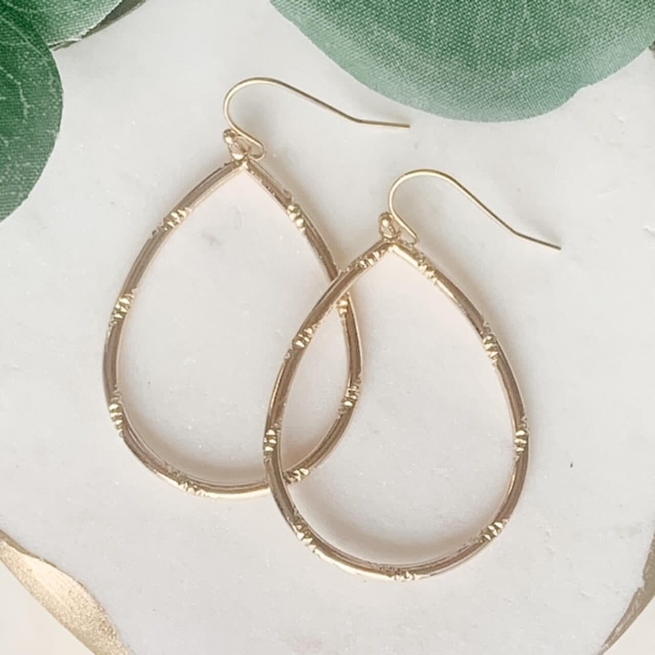 """Shiny gold tone teardrop shaped earrings with diamond-cut texture wrapping diagonally around the hoop. 2""""; hook back; nickel and lead free."""