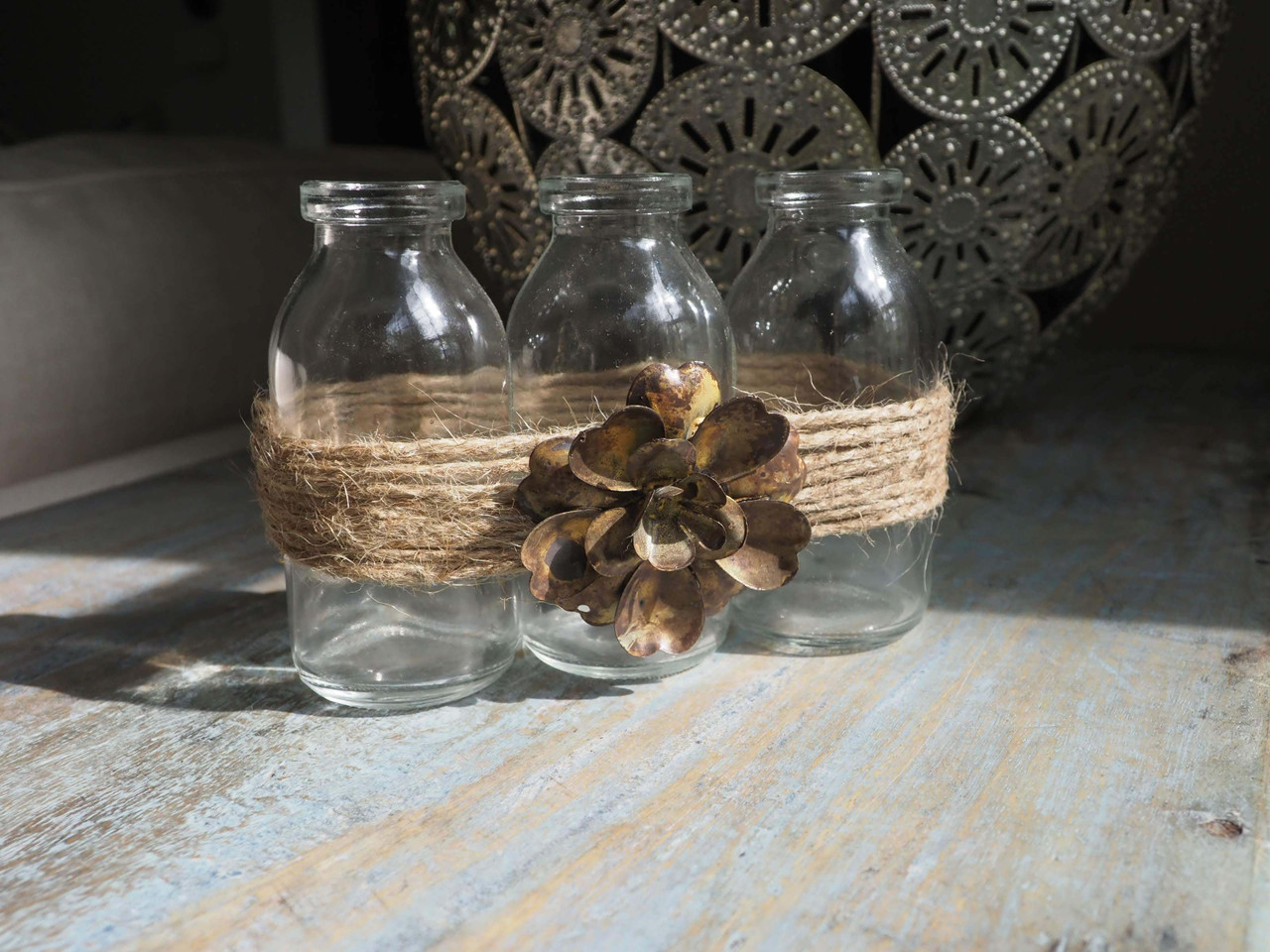 clear glass bottle trio with tied jute