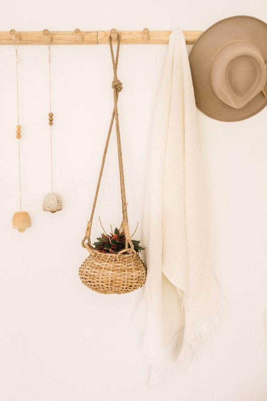 Circular rattan basket hanging from three jute ropes