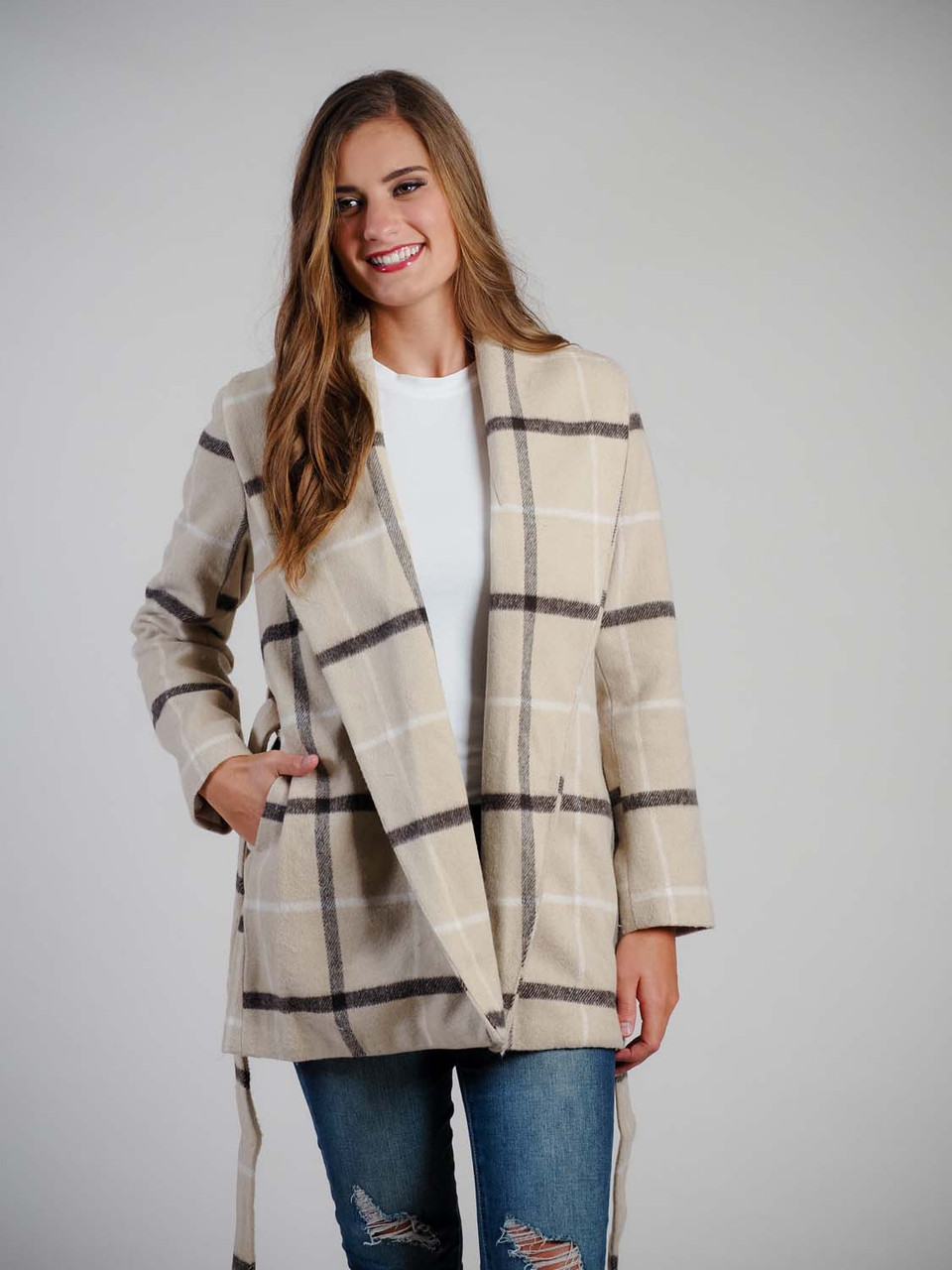 Tan, black, and white plaid coat features a relaxed fit, oversized lapel, matching belt to tie at waist, and a lined interior
