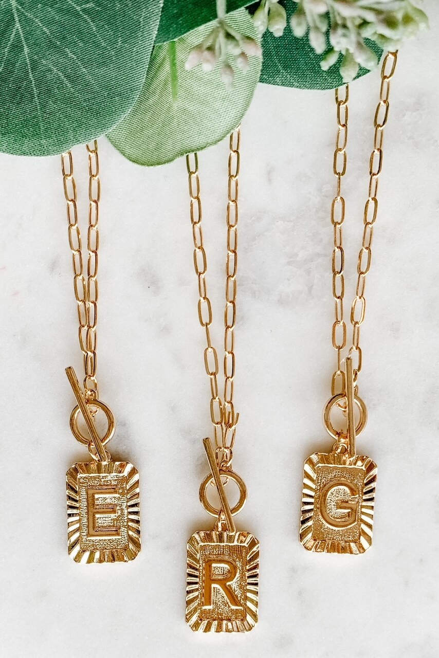"""Gold-tone necklace and 5/8"""" x 7/8"""" rectangle charm with embossed initial on textured background with starburst cut border. Available letters: A B C E G HJKLMNPR ST. 16"""" with toggle clasp. Nickel and lead free."""