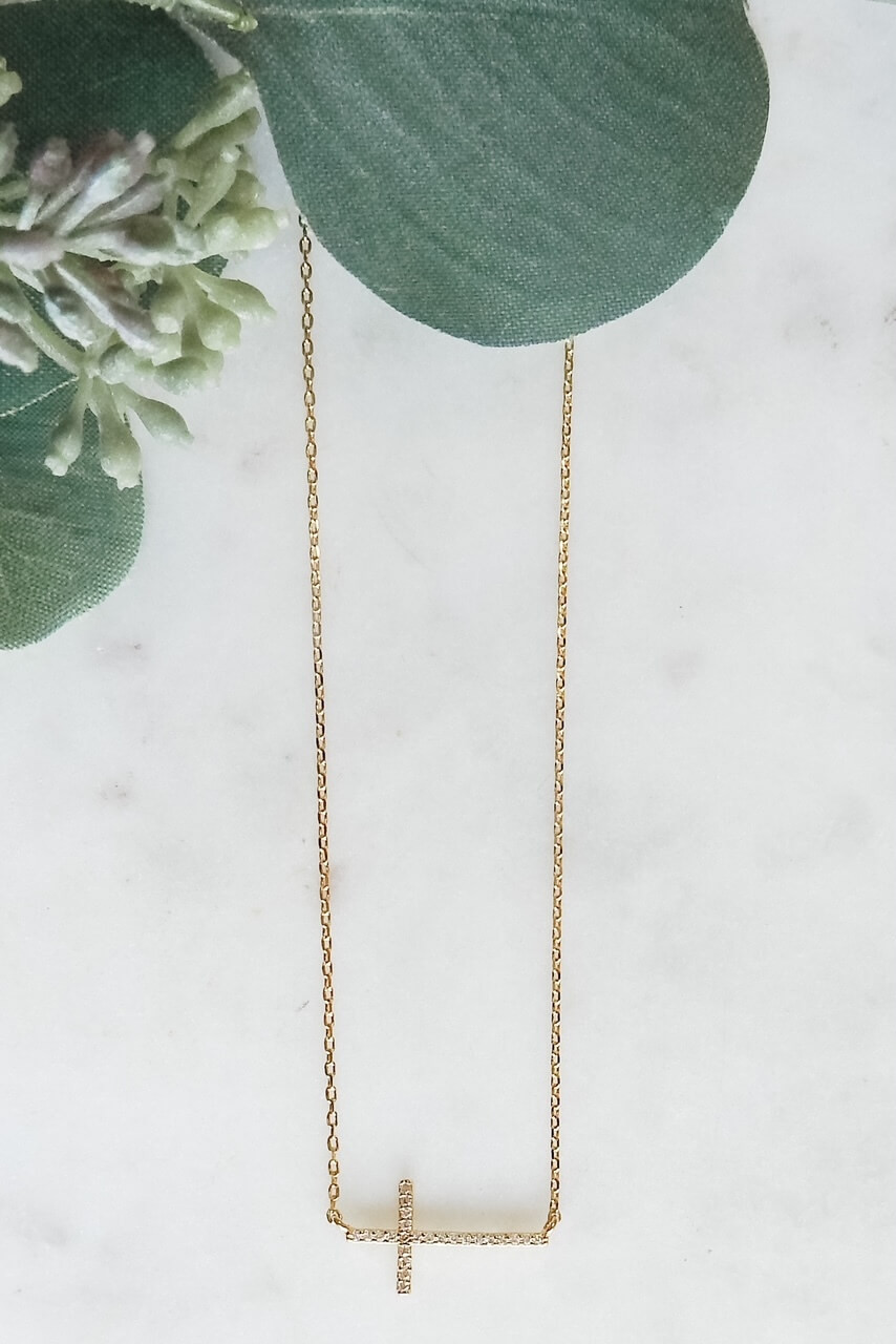 """Gold dipped dainty necklace with 3/4"""" x 3/8"""" sideways CZ lined cross. Adjustable from 15.5"""" - 17.5"""" with lobster claw clasp. Nickel and lead free."""