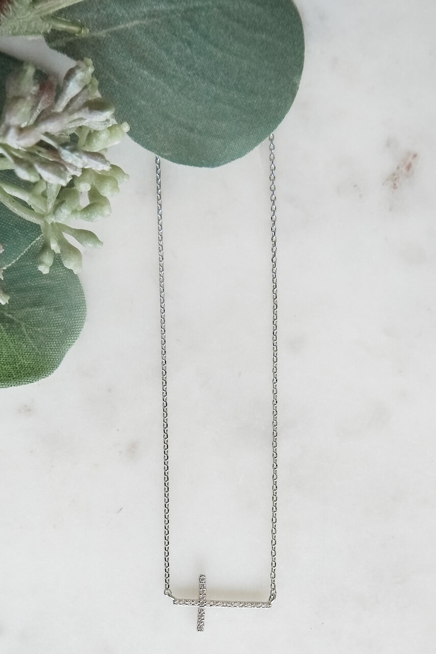 """White gold dipped dainty necklace with 3/4"""" x 3/8"""" sideways CZ lined cross. Adjustable from 15.5"""" - 17.5"""" with lobster claw clasp. Nickel and lead free."""