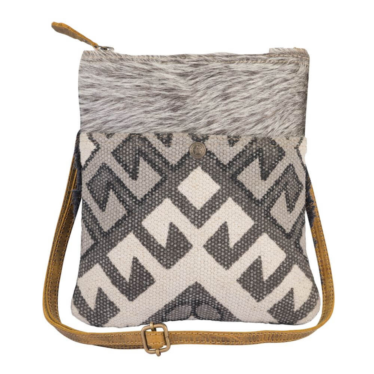 """This crossbody bag has angled aztec patterns in shades of gray on the front with gray cowhide accent at the top and dark gray fringe detail around the sides and bottom. Canvas back, fully lined slip pocket on front with snap close, zipper pocket on back; adjustable/removable shoulder strap; zipper close at top; interior is fully lined.8.5"""" wide, 10.75"""" high."""
