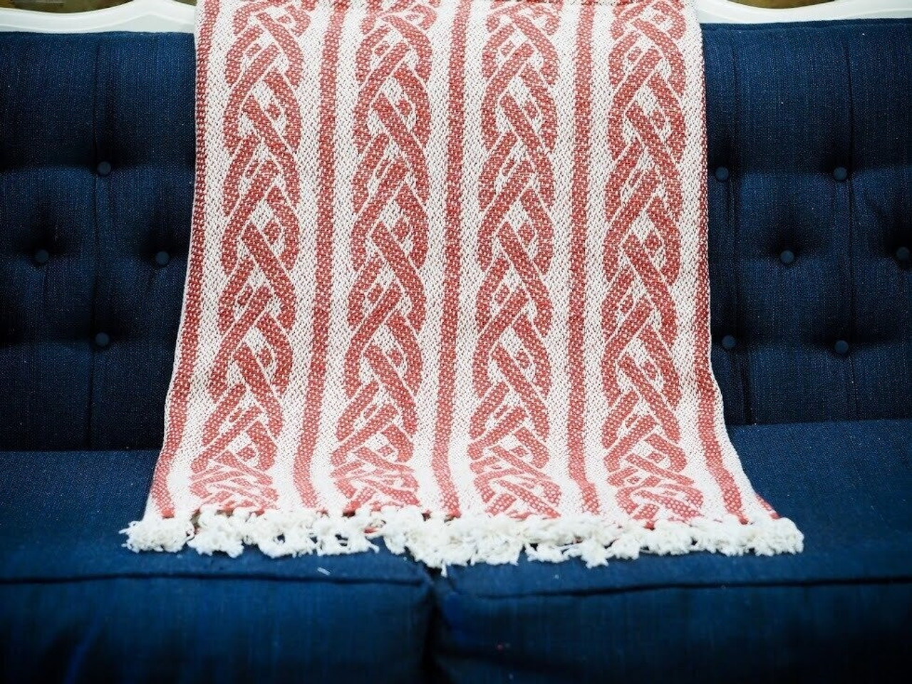 A Red and White Throw Blanket Hangs on a Navy Blue Couch