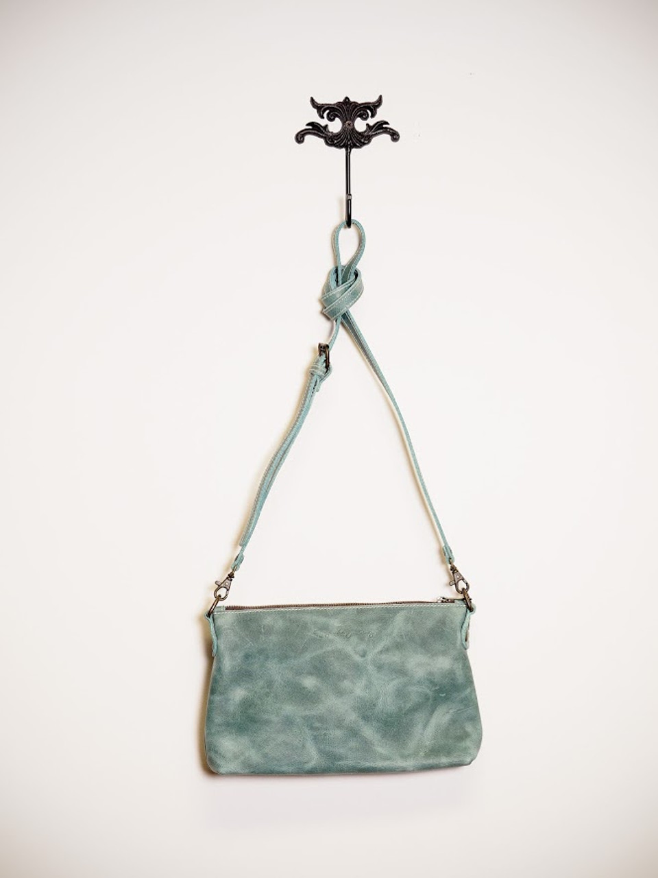 Turquoise, Suede Purse Hangs on Wall Hook