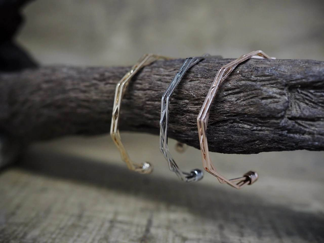 Silver, Gold, and Bronze Bangle Bracelets Hang on Tree Branch