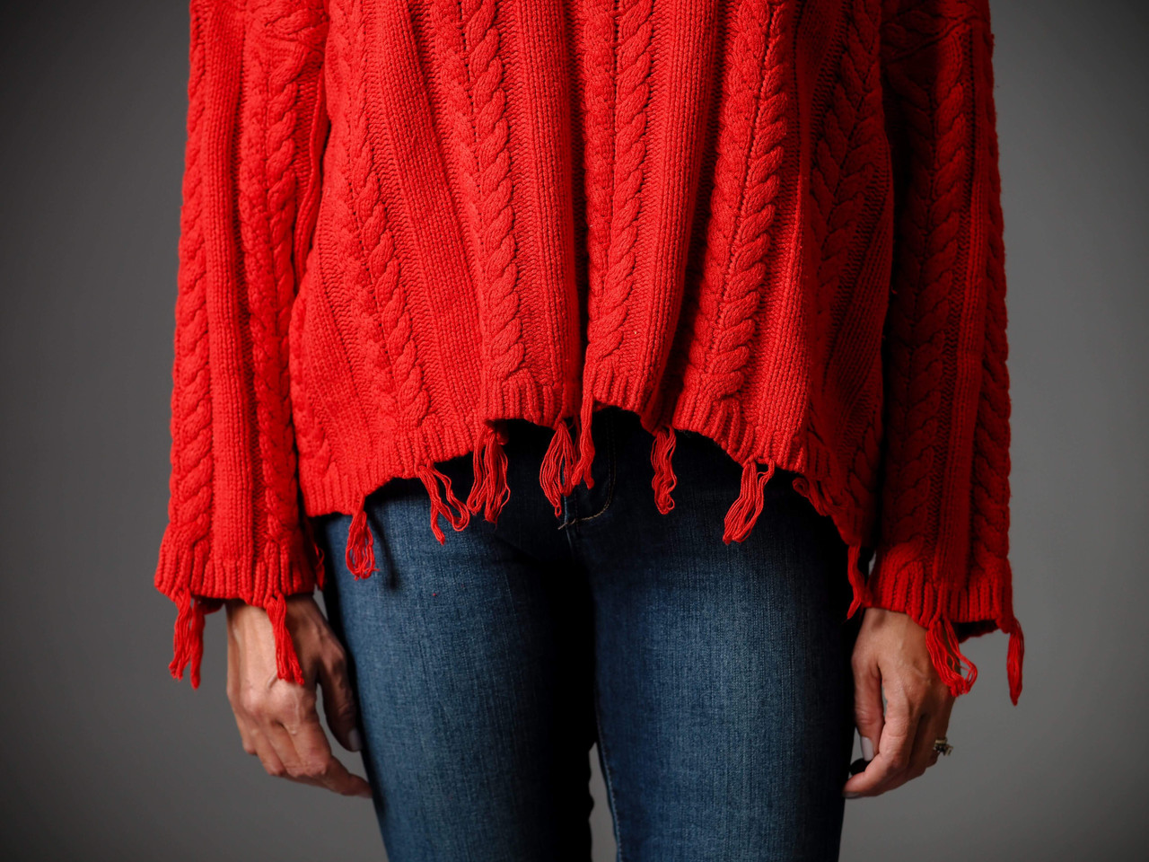 red cable knit cropped sweater with frayed detail