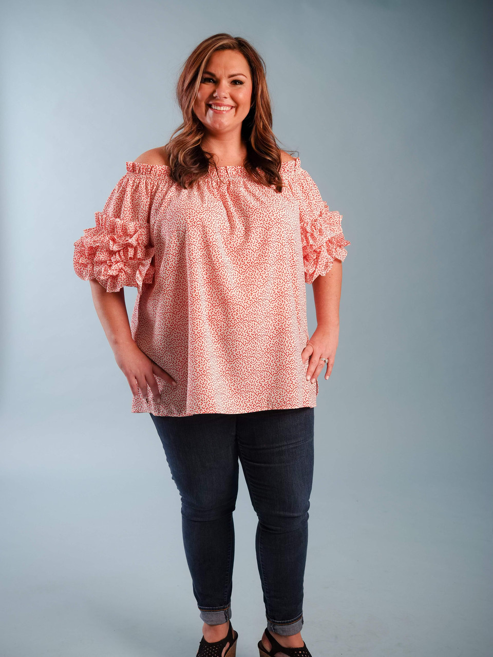 Lightweight off-the-shoulder blouse with adorable tiny red heart print, Ruffled sleeve detail, Model is wearing a 1X.