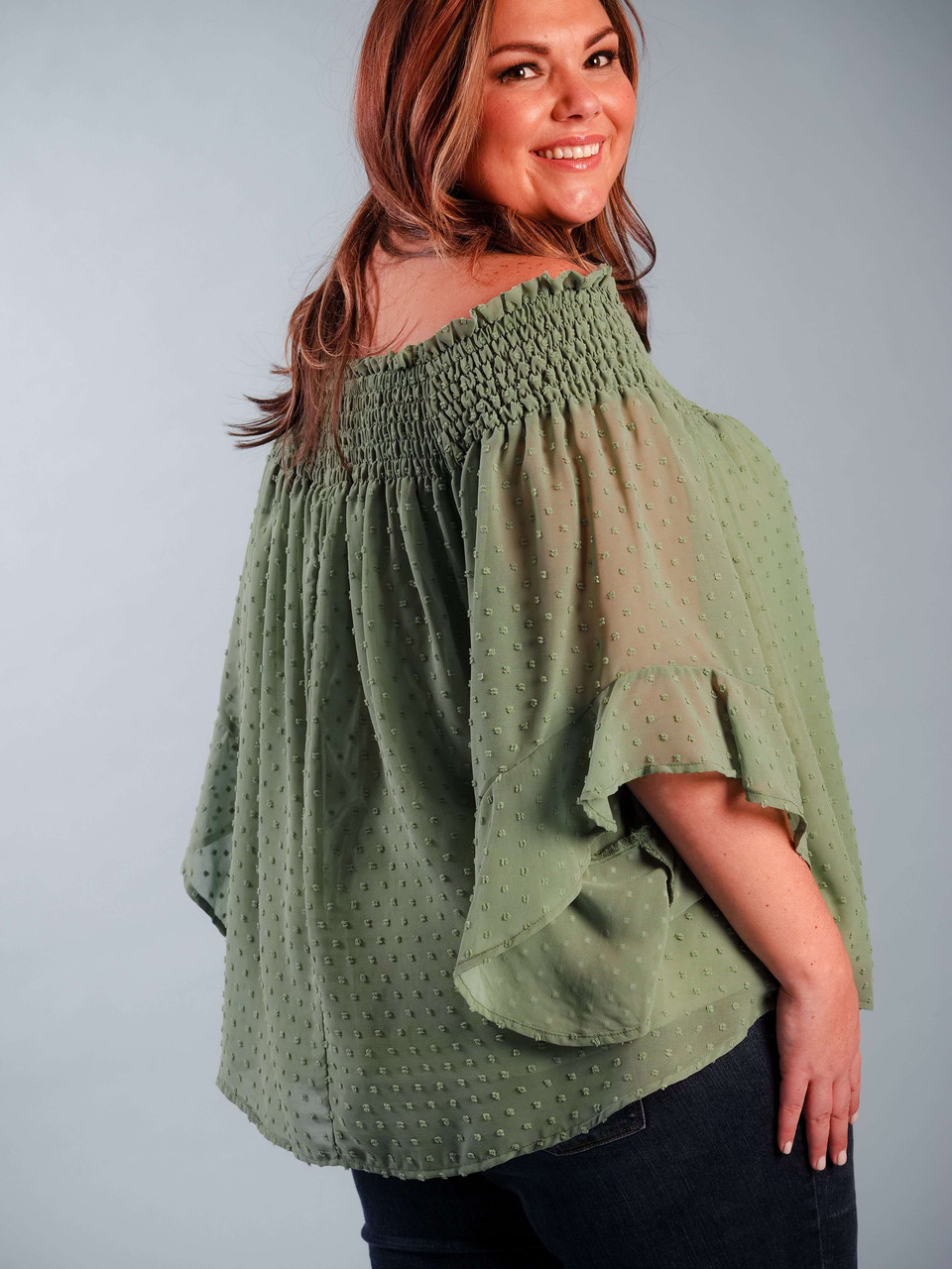 Lightweight sage green blouse, Lined & off-the-shoulder, Ruffled sleeve detail, Model is wearing a XL.