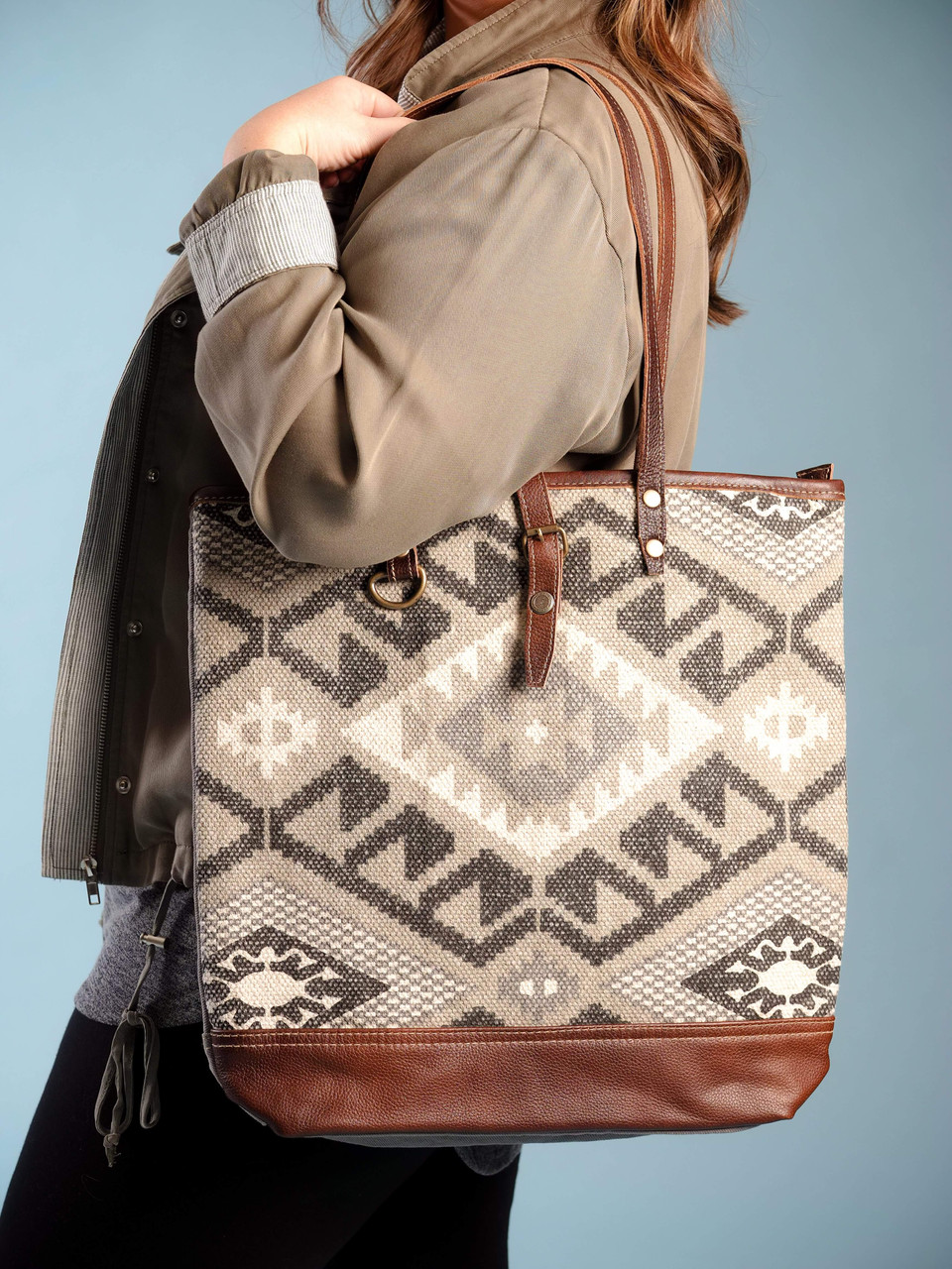 Leather, canvas & rug tote. The front has a natural, grey and blue southwest print and the back is plain canvas with a zipper closure.Interior has double open pockets and a single pocket with zipper.