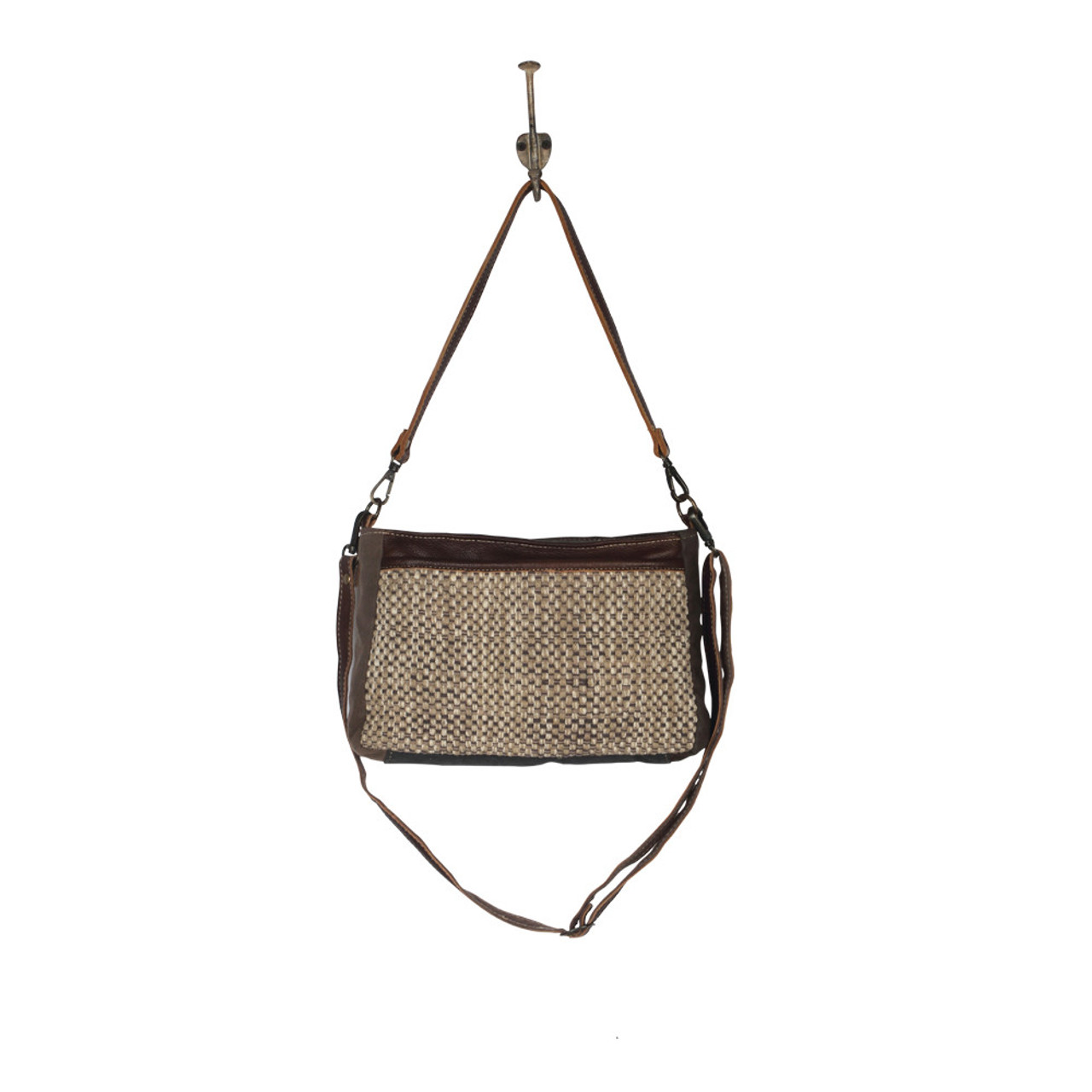 Leather, canvas & rug tote. The front has a neutral woven pattern with main zipper closure and a hidden large front pocket with zipper. The back is solid canvas, also with a hidden pocket and zipper. Interior has a single pocket with zipper. Included are two shoulder straps, one short and the other long with ability to adjust.
