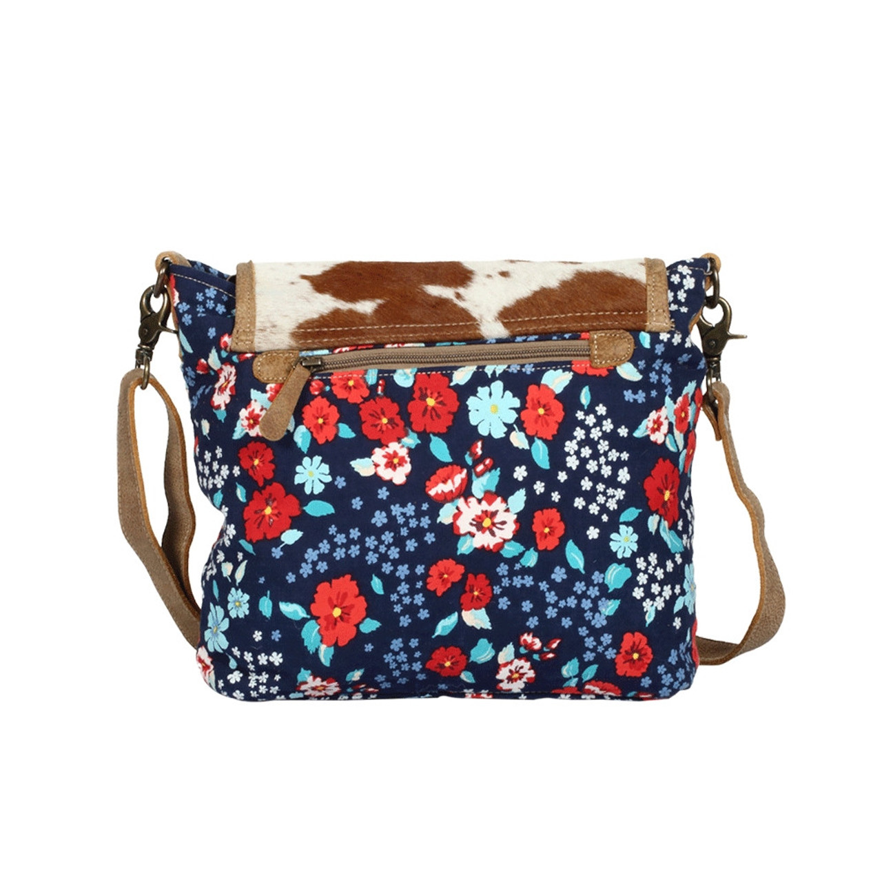 Hairon, canvas & leather accent tote with a beautiful floral canvas and a hairon accent flap closure with clasp and main zipper closure for added security. An exterior back pocket with zipper and the interior has double open pockets and a single pocket with zipper.