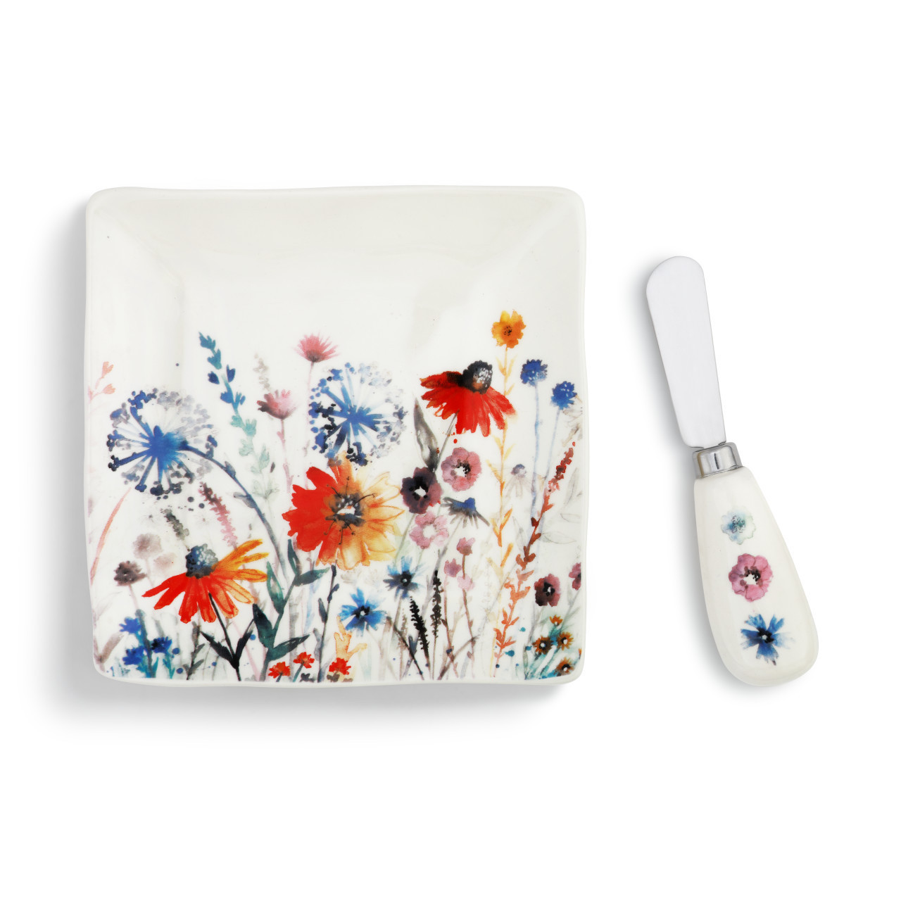 The spreader is crafted from stainless steel with a ceramic handle, while the plate is made of glazed stoneware. Featuring prominently on both items is a red and blue floral scene reminiscent of a meadow in the summertime.