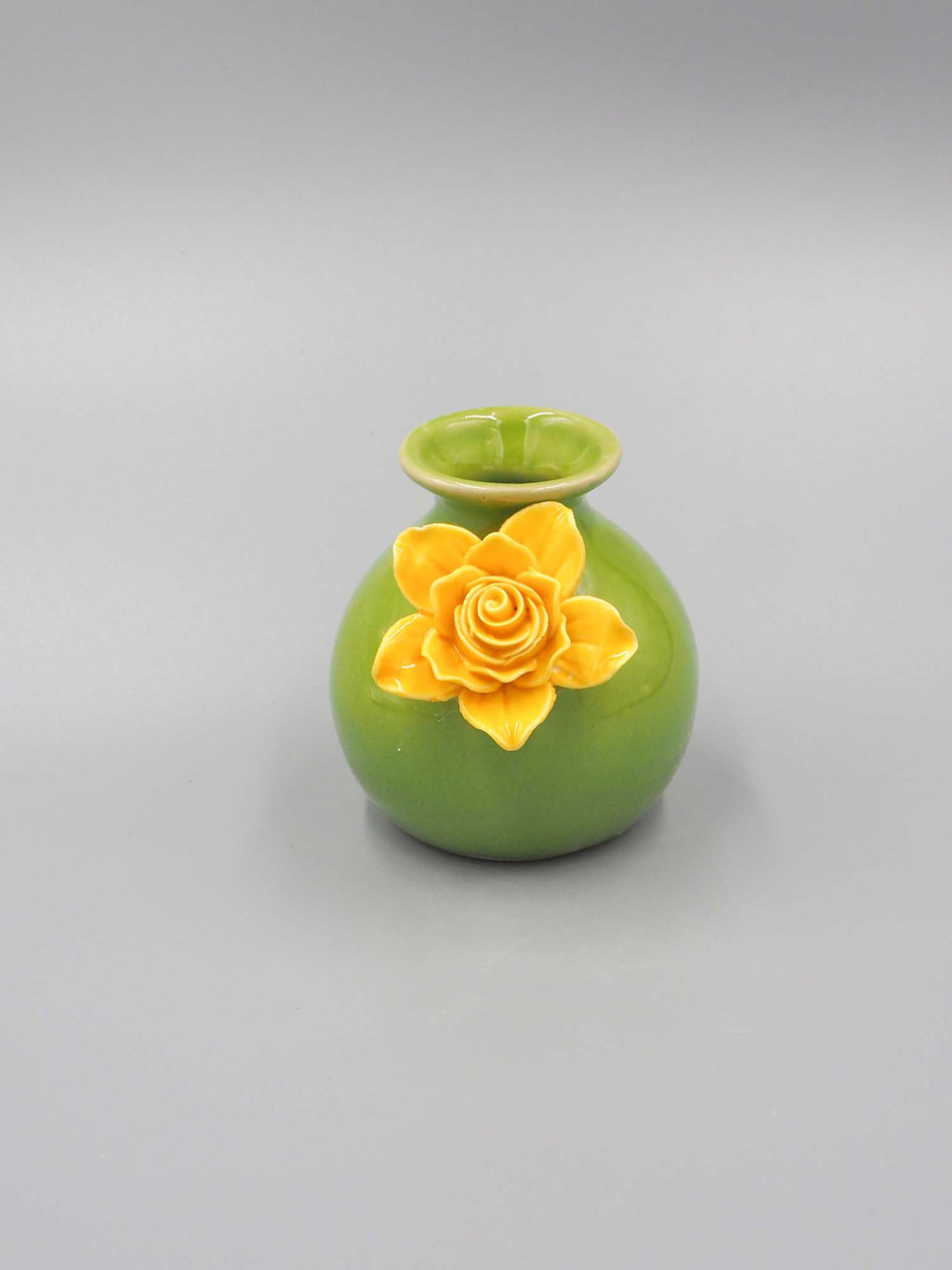 green ceramic bud vase with yellow flower