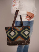 geometrical pattern on the front and the brownish gray denim on the back of the Tote Bag gives it a classical vibe. Zipper close at top, outside zipper pocket on back, interior has a zipper pocket on one side and two slip pockets on the other.