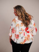 Red, gold, grey, green floral print on soft white blouse. Seamed at waist with elastic gathering in back; kimono style sleeves