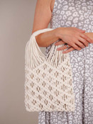 Macrame net satchel with cord wrapped handles. Creamy beige canvas inside pouch has a stone and white all-over leopard print, full lining, zipper pocket inside, and zipper close.
