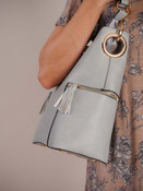Soft greyish blue vegan leather tote with black edging at seams and gold tone hardware. Zipper close at top and side pockets with tasseled zipper close. Choose to use the shoulder strap or the adjustable crossbody strap. Inside is fully lined and features two slip pockets, 2 zipper pockets, and a small compartment to keep your items accessible.
