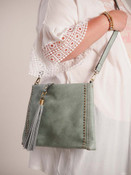 Soft light teal vegan leather crossbody bag with adjustable removable strap to carry as a crossbody, shoulder bag, or a clutch. Fold-over front tassel, studded and woven detail