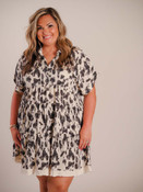 Medium and dark gray abstract pattern on creamy colored dress. Pointed collar, v-neck opening, cuffed short sleeves, three tiered seams, pleated detail at top seam in back, freyed linen ribbon detail at bottom