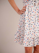 """Charming summer dress. V-neck with ruffle detail and three buttons to elastic waist; wide matching belt to tie; sleeveless; ruffle detail at shoulder; fully lined; 5"""" ruffle detail at hem"""