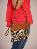This hairon bag keeps it classy with embossed leather and makes it fun with leopard print. Two strap options make it a must–have. Leather wrist strap and adjustable/removable crossbody strap; hairon on front; leather on back and top of front; zipper close at top; interior is fully lined and has one zipper pocket and two slip pockets.
