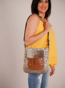 A unique blend of embossed leather, hairon, hand-woven rug form this crafty looking shoulder bag. Slip pocket on front with flap close and magnet snap on leather loop; zipper pocket on canvas back; adjustable/detachable shoulder strap; fully lined inside with a zipper pocket and two slip pockets.