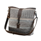 Upcycled from a unique patterned rug; hairon accent on front; canvas back and bottom; leather accents. Adjustable/removable shoulder strap; zipper pocket at back; zipper close at top and leather flap that clips to bottom of bag; interior is fully lined and has one zipper pocket and two slip pockets