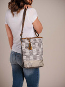 Subtle checker board pattern on upcycled woven rug piece of this bag; hairon at the bottom of the front; leather details; military tent canvas at base and back. Zipper pockets on back; adjustable/removable shoulder strap; zipper close at top; interior is fully lined and has one zipper pocket and two slip pockets.
