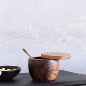 """This visually appealing and useful Acacia Wood lidded jar comes with its own spoon. The lid pivots on a wood pin to open. It's great for salt, spices, sweeteners, or any other little condiment you can get in there. 3-1/2"""" Round x 3""""H; hand wash only."""