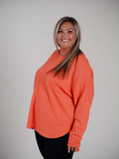 Orange pull-over tunic with ribbed texture slanted towards a middle seam in front and back to create a v-pattern. Wide round neck, slouched shoulders, long sleeves, slightly longer in back.