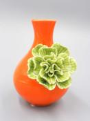 orange bud vase with green flower