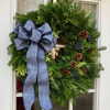 Bar Harbor fresh Christmas wreath with blue bow, pine cones, faux blueberries shown on door