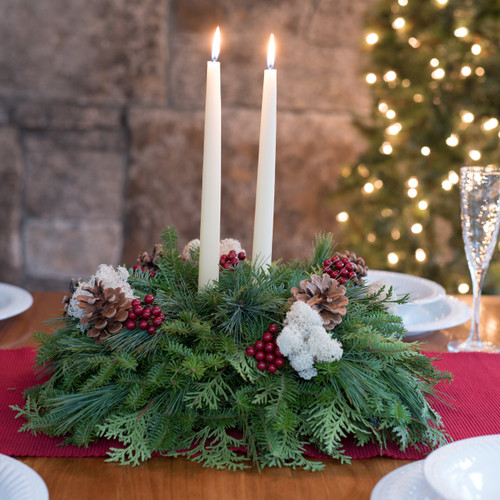 Winterberry centerpiece with pine cones, reindeer moss, faux winterberries, and ivory candles.