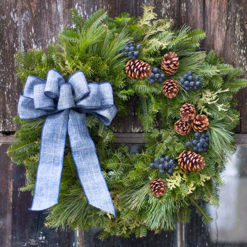Bar Harbor fresh Christmas wreath with blue bow, pine cones, faux blueberries shown on old shack with moss on roof