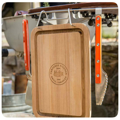 The PK Grills Durable Teak Cutting Board has a unique stainless steel bar for hanging it on the accessory bar of your PK360 Grill or Original PK.