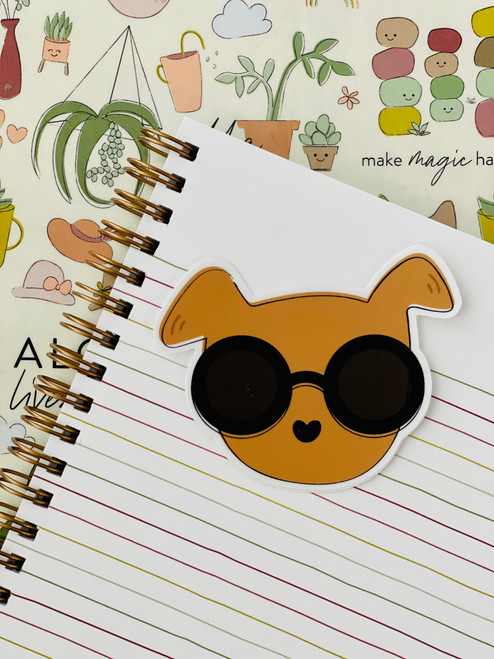 adhesive sticker in the shape of a brown dog with sunglasses on