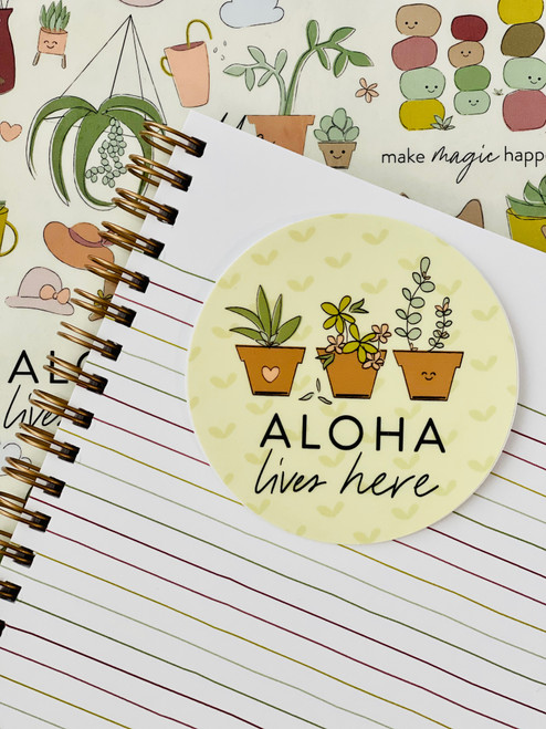 """round 3"""" sticker with yellow background and 3 planted succulents with text aloha lives here with lives here in script"""