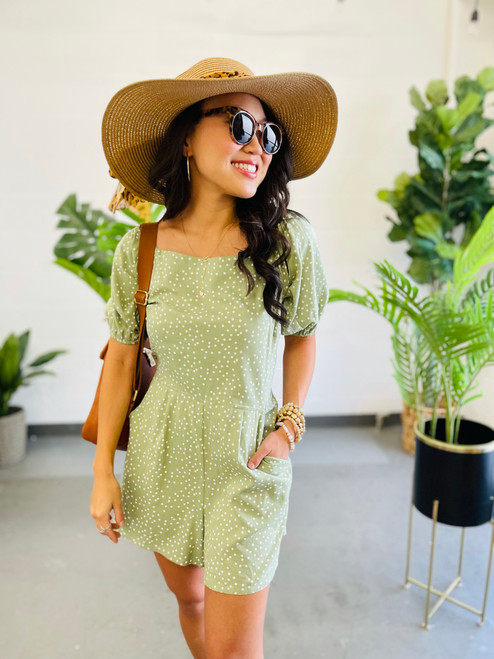 woman wearing a sage green polka dot romper with smocked back, puff sleeves and tie back detail on shoulder area