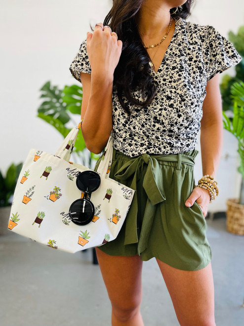 woman wearing a pair of olive shorts with pleated details and bow tie