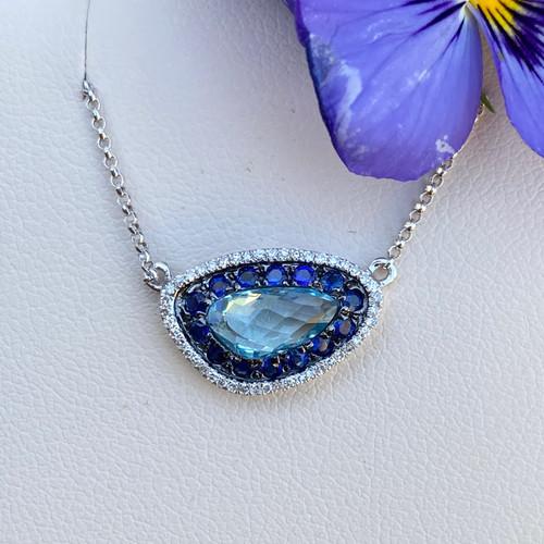 BLUE TOPAZ, SAPPHIRE, AND DIAMOND HALO PENDANT